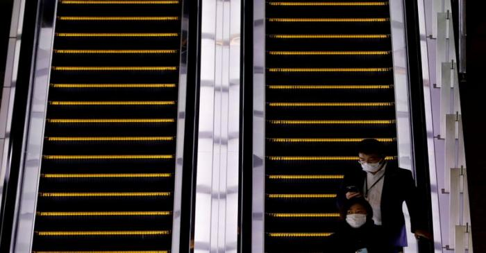 FILE PHOTO:  Pedestrians wearing facial masks ride an escalator at a business district in Tokyo