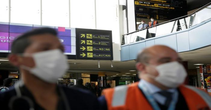 FILE PHOTO:  El Alto Airport workers wearing protective masks are seen following the outbreak