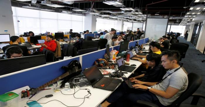FILE PHOTO: Employees of Traveloka are seen working at the company's headquarters in Jakarta