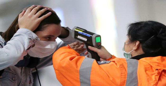 FILE PHOTO: A worker checks the temperature of a passenger arriving into Hong Kong