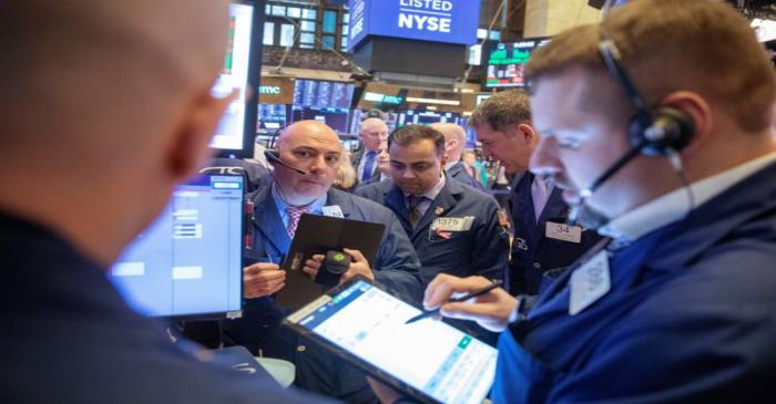 Traders work on the floor of the New York Stock Exchange shortly after the opening bell in New