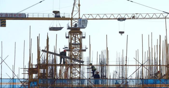 FILE PHOTO: Vanke sign is seen above workers working at the construction site of a residential
