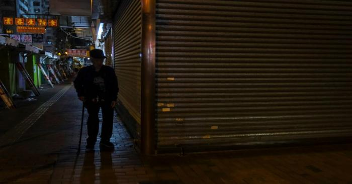 A man walks past a closed shop following the outbreak of the new coronavirus, in Hong Kong