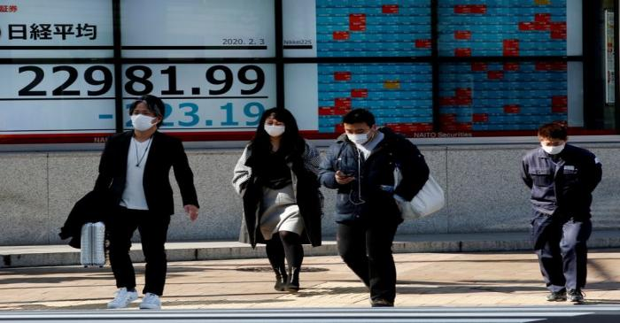 FILE PHOTO: People wearing surgical masks walk past a screen showing Nikkei index outside a