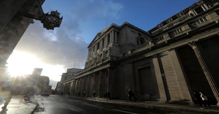 Pedestrians walk past the Bank of England in the financial district in London