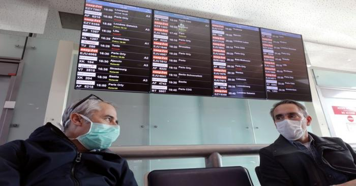 FILE PHOTO: Travellers wearing protective face masks wait for their flights at Nice