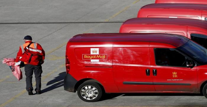 FILE PHOTO: A postal worker carries mail bags from a van at a Royal Mail sorting office in