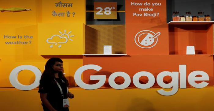 A woman walks past the logo of Google during an event in New Delhi