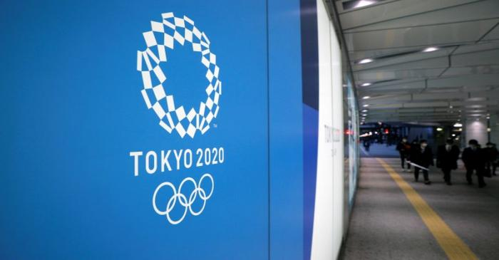 A man wearing a protective mask in front of an advertising billboard of Tokyo Olympics 2020,