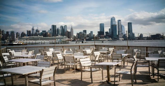 Empty chairs are seen at the deck of a local restaurant that is closed due to the outbreak of