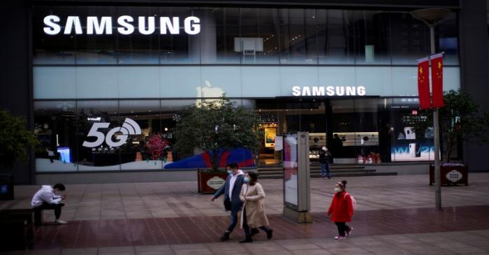 People wears masks in front a Samsung Store at a main shopping area, in downtown Shanghai