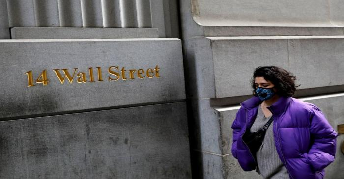 FILE PHOTO: A person wearing a face mask walks along Wall Street after further cases of