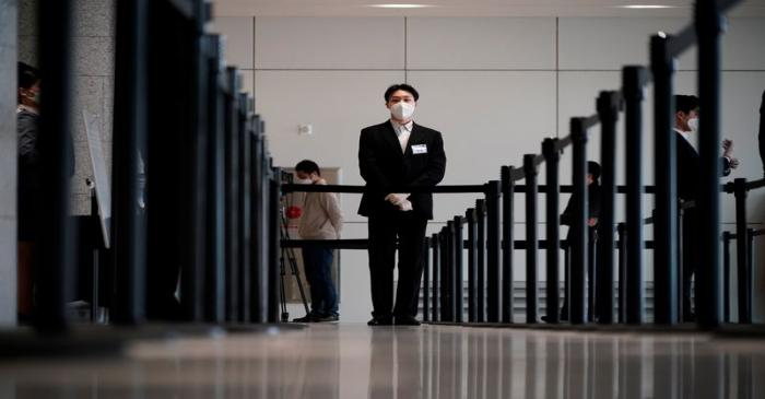 An employee wearing a mask to prevent contracting the coronavirus waits for a shareholder of