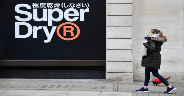 A woman walks past a window display at a Superdry store in London