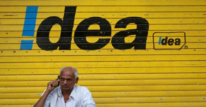 FILE PHOTO: A man speaks on his mobile phone as he sits in front of a shop displaying the Idea