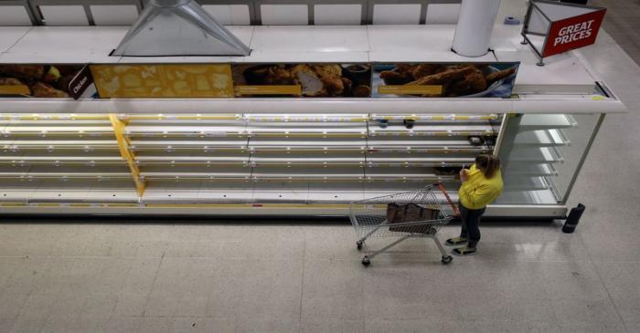 A woman takes a photo of empty shelves at Sainsbury's supermarket