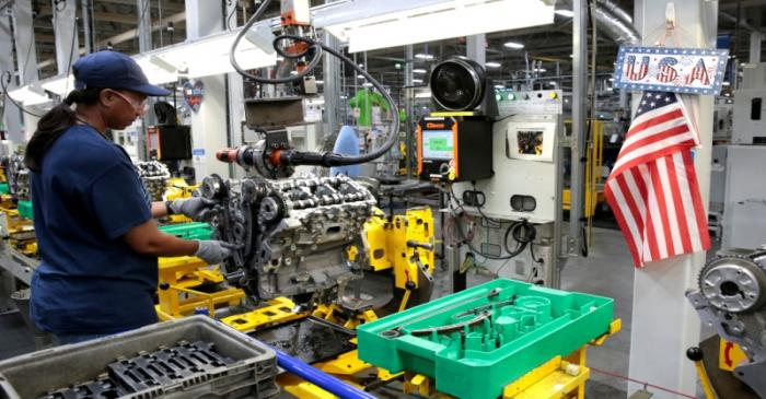 FILE PHOTO: A General Motors assembly worker works on assembling a V6 engine, used in a variety