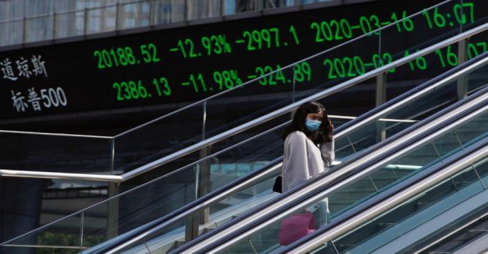 Pedestrian wearing a face mask rides an escalator near an overpass with an electronic board