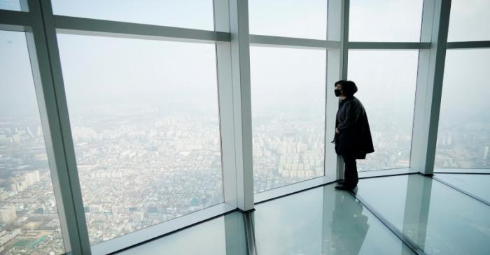A woman wearing a mask to prevent contracting the coronavirus looks at a view of central Seoul