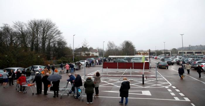 People queue outside of a Sainsbury's supermarket in St Albans