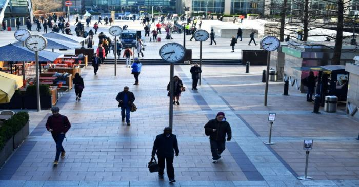 Commuters walk through Canary Wharf in London