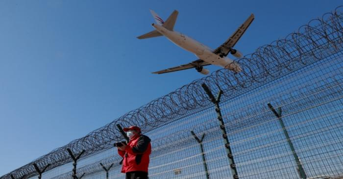 A man wearing a protective mask stands at a fence surrounding Beijing Capital International as