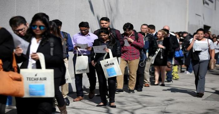 FILE PHOTO: People wait in line to attend TechFair LA, a technology job fair, in Los Angeles