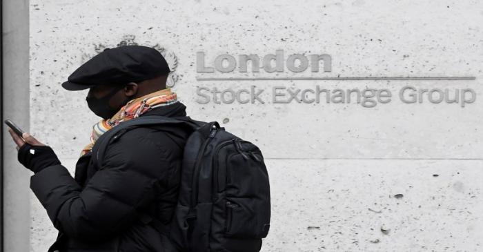 A man wearing a protective face mask walks past the London Stock Exchange Group building in the