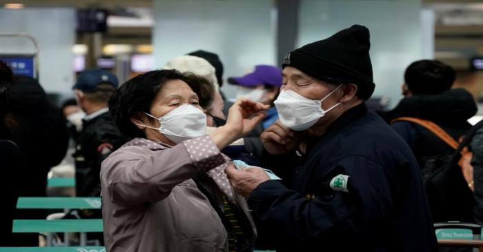 A woman wearing a mask to prevent contracting the coronavirus adjusts her husband's mask as