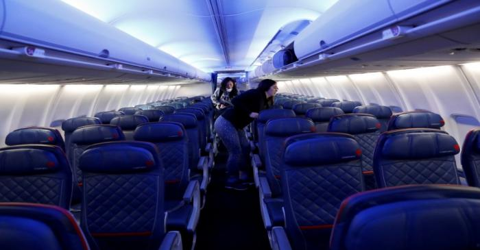 Air travelers grab carry-on luggage behind rows of empty seats aboard a Delta flight from New