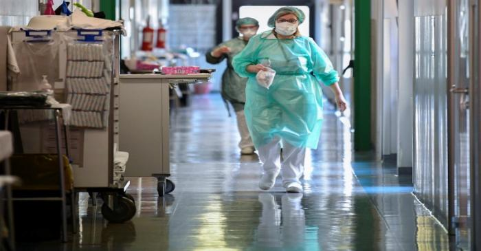 Medical workers wearing protective masks and suits walk in an intensive care unit at the Oglio