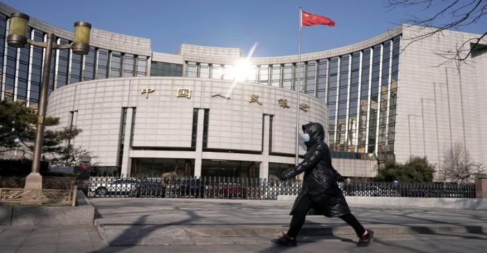 FILE PHOTO: Man wearing a mask walks past the headquarters of the People's Bank of China, the
