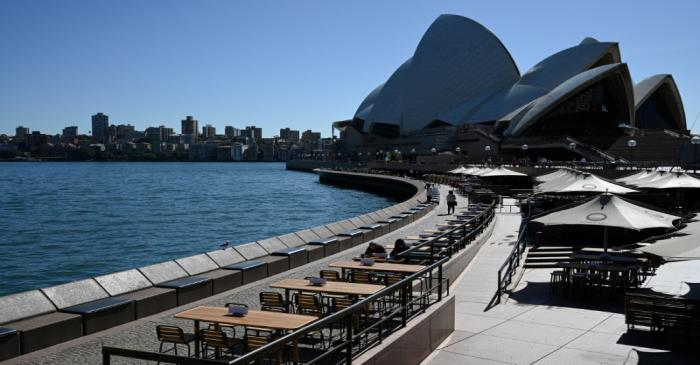 Tables at an open restaurant are seen mostly deserted on a quiet morning at the waterfront of