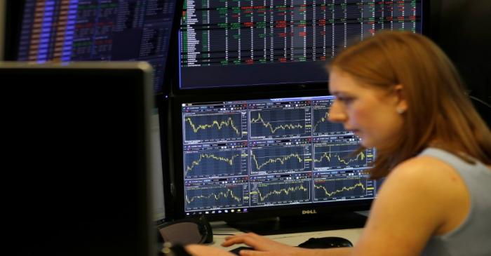 A financial trader works at their desk at CMC Markets in the City of London