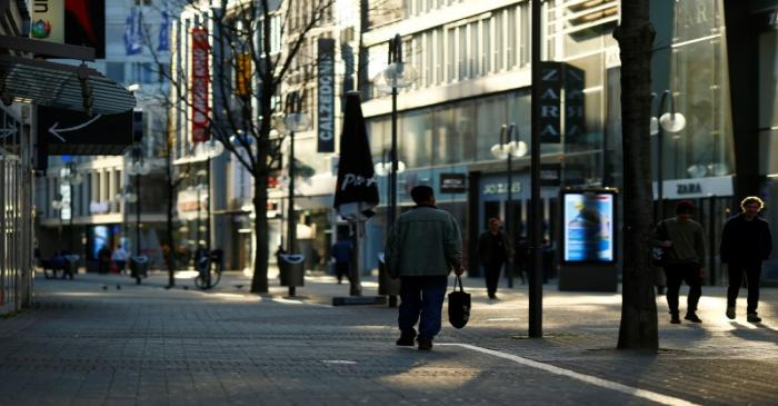 People walk in the main shopping street as shops are closed during the spread of the
