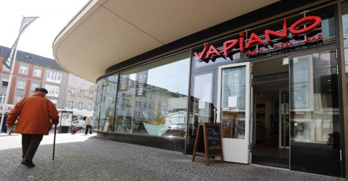 FILE PHOTO:  A man walks past an open Vapiano restaurant during the spread of coronavirus