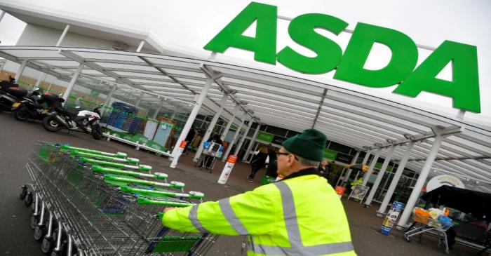 FILE PHOTO: A worker pushes shopping trolleys at an Asda store in west London, Britain