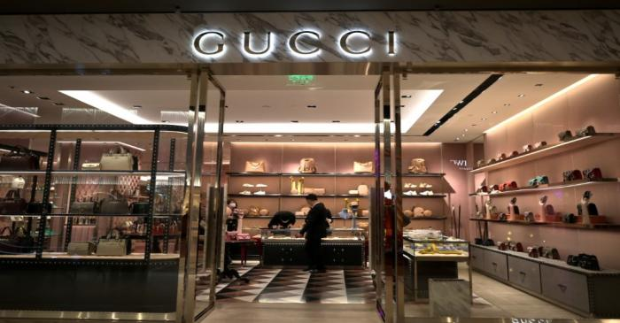 FILE PHOTO: Staff members wearing face masks are seen inside a store of an Italian luxury brand