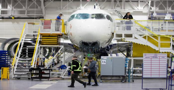 FILE PHOTO: Employees work on an Airbus A220-300 at their facility in Mirabel
