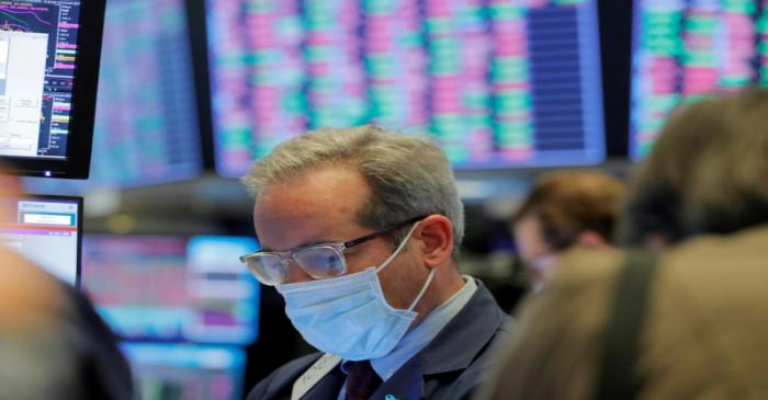FILE PHOTO: A trader wears a mask as he works on the floor of the New York Stock Exchange