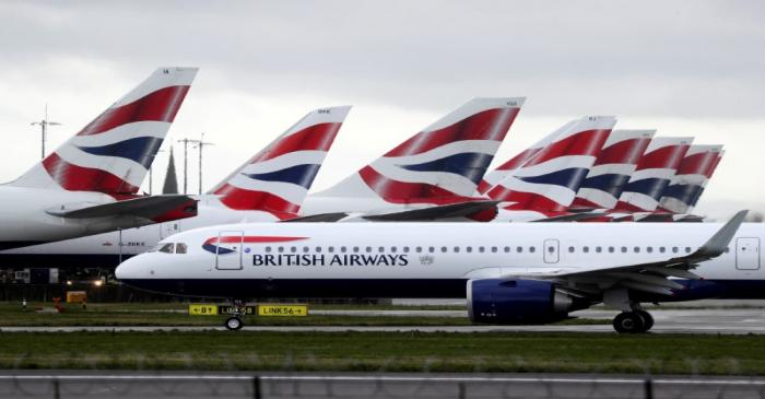 A BA plane taxis past parked aircraft near Terminal 5 at Heathrow Airport