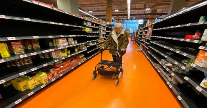 FILE PHOTO: A shopper walks through an aisle empty of pasta, rice, beans and soup at a Loblaws