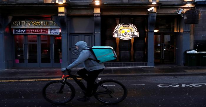 A Deliveroo driver goes past a bar as the spread of the coronavirus disease (COVID-19)