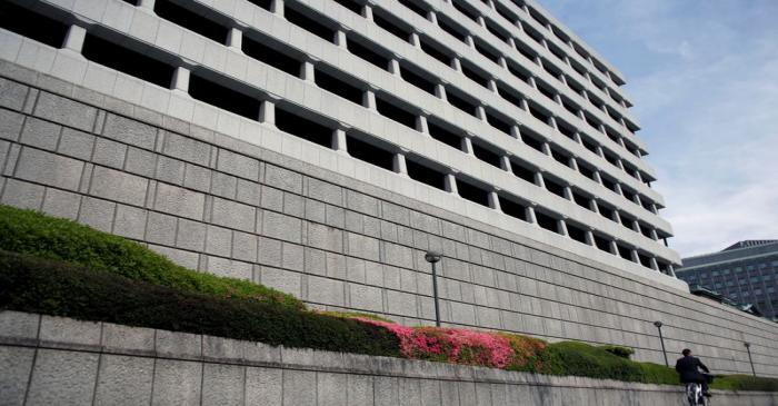 Man riding bicycle rides past the Bank of Japan building in Tokyo