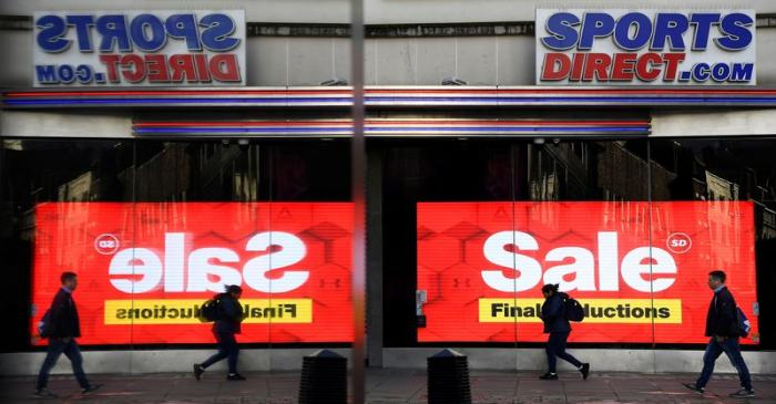 Pedestrians are seen reflected in a window as they pass a branch of Sports Direct on Oxford