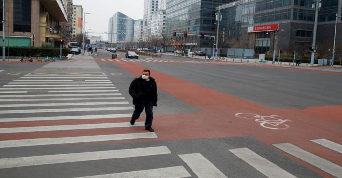 FILE PHOTO: A man wears a face mask as he crosses a street in the Central Business District in