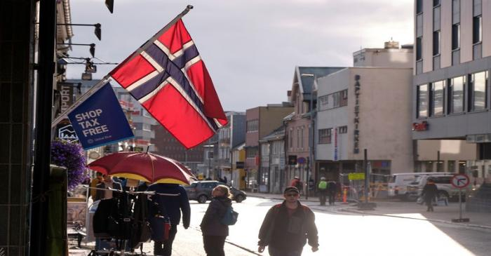 A Norwegian flag flutters over a shop in Tromso