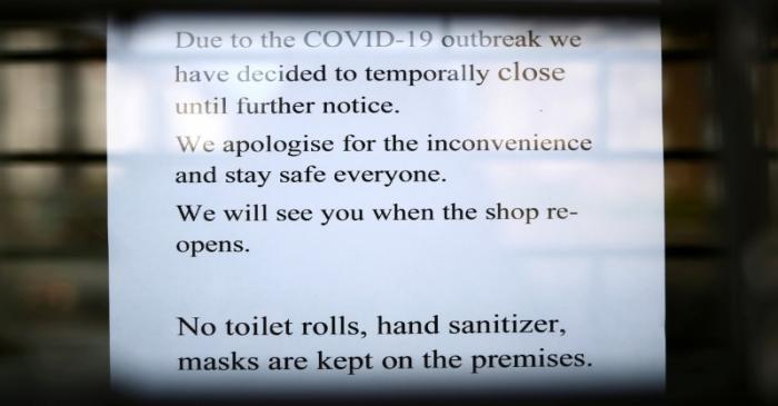 FILE PHOTO: A sign is seen on the front of a shop informing customers it is closed due to the