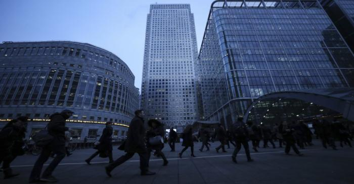 Workers walk to work during the morning rush hour in the financial district of Canary Wharf in