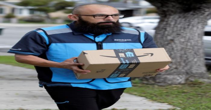 Danny Gonzalez walks with a package when he delivers for Amazon during the outbreak of the